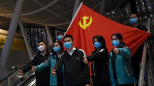 Du personnel médical pose devant un drapeau chinois à la gare de Wuhan avant de quitter la ville, le 18 mars 2020.