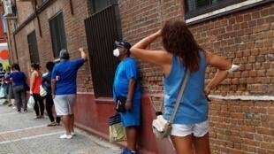 أشخاص يصطفون بانتظار تلقي مساعدات غذائية في مدريد، 2 يونيو/حزيران 2020.