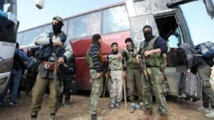 """مقاتلون من """"هيئة تحرير الشام"""" في ريف حلف الجنوبي بعد إخراجهم من مخيم اليرموك، الثلاثاء 1 أيار/مايو 2018"""