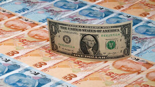 Un billete de un dólar sobre billetes de 50 y 100 liras turcas.