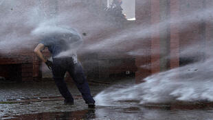 A demonstrator is hit by a jet from a water cannon during a protest in homage to the victims of Chile's 1973 military coup, in Santiago, September 2020