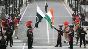 حراس باكستان (يرتدون الزي الأسود) وضباط قوة أمن الحدود الهندية يرفعون أعلامهم الوطنية خلال عرض عسكري في يوم الاستقلال الـ 72 لباكستان، بالقرب من لاهور ، باكستان 14 آب/أغسطس 2019.