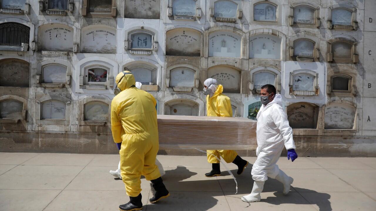 Trabajadores funerarios llevan un ataúd con el cuerpo de una persona que murió por coronavirus, en un cementerio en Lima, Perú, 9 de mayo de 2020.