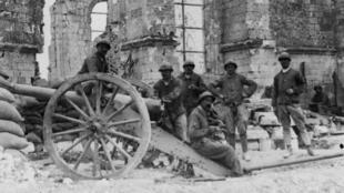 Les restes de l'église de Fay dans la Somme avec au premier plan un canon de 90 mm en batterie et des soldats français, en août 1916.