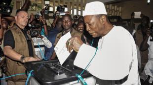 Photo d'archive montrant le président sortant Alpha Condé glisser son bulletin dans l'urne lors de la présidentielle en Guinée le 11 octobre.