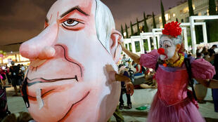 An Israeli woman in a clown's outfit mocks a giant head of Prime Minister Benjamin Netanyahu at a demonstration in the coastal city of Tel Aviv against a second nationwide lockdown to tackle a spike in coronavirus cases