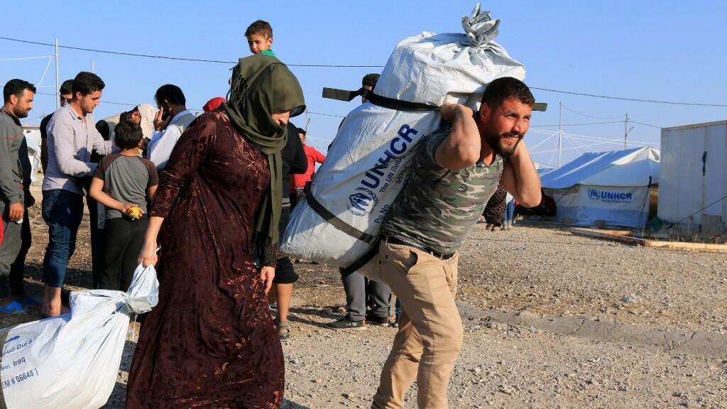 Familias desplazadas sirias, que huyeron de la violencia después de la ofensiva turca en Siria, reciben ayuda en el campo de refugiados de Bardarash en las afueras de Dohuk, Iraq el 22 de octubre.