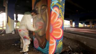 Harold Castañeda pinta el rostro de Carlota Salinas, víctima de la violencia, debajo de un puente en Bogotá, el 4 de febrero de 2021