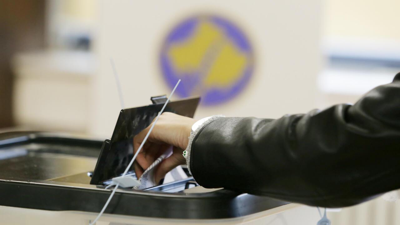Un électeur glisse son bulletin dans l'urne dans un bureau de vote à Pristina, le 6 octobre 2019.