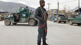 An Afghan policeman stands guard near the site of an attack in Kabul, Afghanistan March 25, 2020.
