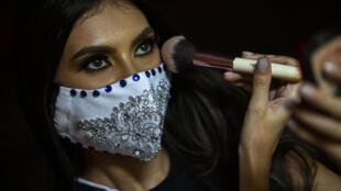 """Ana Marcelo, concursante de """"Miss Nicaragua"""", lleva una máscara facial contra la propagación del nuevo coronavirus mientras se maquilla antes de una presentación antes del evento, el 22 de julio de 2020 en Managua"""