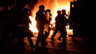 Des policiers poursuivent des manifestants qui ont incendié plusieurs bâtiments lundi soir à Ferguson après la décision du grand jury de ne pas poursuivre le policier qui a tué Michael Brown.