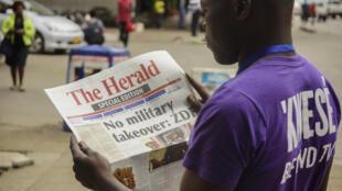 Un habitant d'Harare lisant la presse au lendemain du coup de force de l'armée au Zimbabwe.