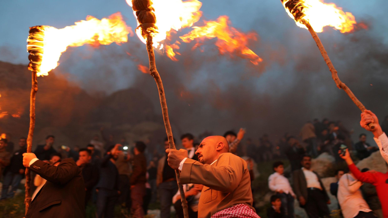 Los hombres kurdos iraquíes llevan antorchas de fuego mientras celebran el Día de Nouruz , un festival que marca el primer día de la primavera y el año nuevo, en la ciudad de Akra, cerca de Duhok, en el Kurdistán iraquí, Irak, 20 de marzo de 2019.
