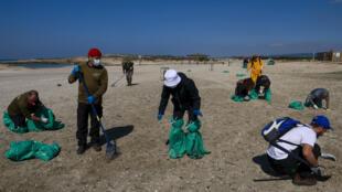 متطوعون إسرائيليون يعملون على تنظيف شاطئ هبونيم جنوب مدينة حيفا الساحلية في 21 شباط/فبراير 2021ـ بعد تسرب مادة القطران من إحدى السفن وحذرت السلطات الجمهور من الاقتراب من الشواطئ