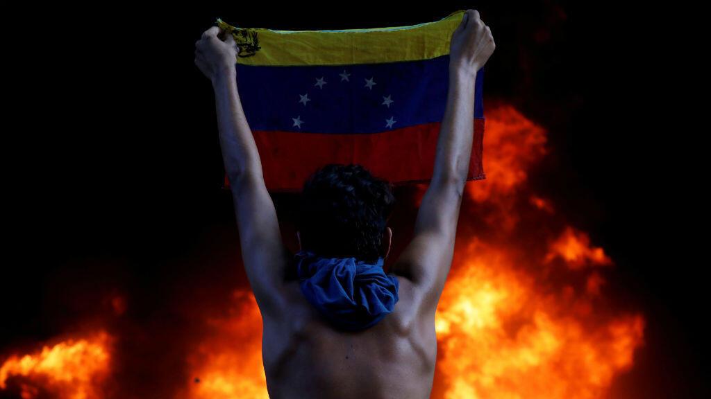 Conflicto en Venezuela:  un manifestante sostiene la bandera nacional  al frente de la Corte Suprema de Justicia. El fuego fue propiciado por venezolanos que manifiestan el rechazo al gobierno de Nicolás Maduro. Esta imagen fue capturada el 12 de junio.