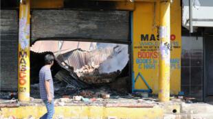 Un hombre camina frente a un comercio dañado, tras los disturbios y saqueos de la noche anterior, en el municipio de Alexandra, Johannesburgo, Sudáfrica, el 3 de septiembre de 2019.
