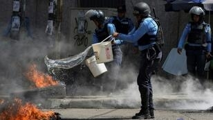 Police try to put out tires set ablaze in a Honduras opposition demonstration on January 27, 2019