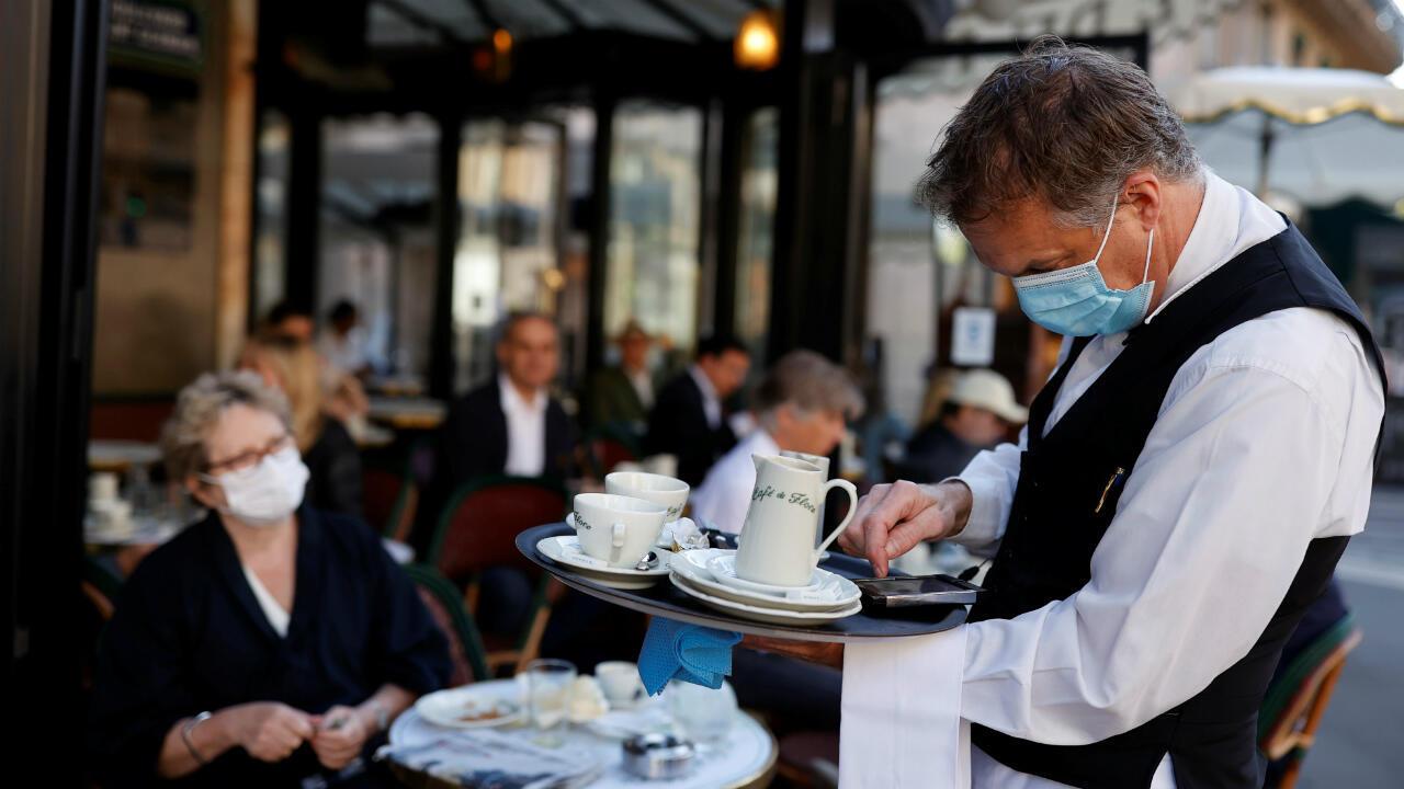 Un camarero que lleva una máscara facial atiende a los clientes en el Café de Flore, mientras los restaurantes y cafés se abren después del brote de la enfermedad por coronavirus (COVID-19), en París, Francia, el 2 de junio de 2020.