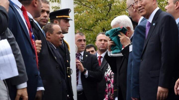 -الرئيس عباس يقبل العلم الفلسطيني قبل رفعه أمام مقر الأمم المتحدة