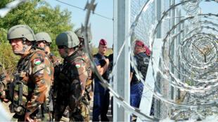 Des policiers et des militaires hongrois se tiennent près de la clôture installée à la frontière avec la Serbie, le 14 septembre 2015.