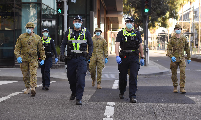 Des policiers et des soldats en patrouille à Melbourne (Australie) le 2 août 2020 après l'instauration d'un couvre-feu en raison du coronavirus.