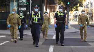 Police and soldiers patrol the Docklands area of Melbourne on August 2, 2020, after the curfew was imposed.