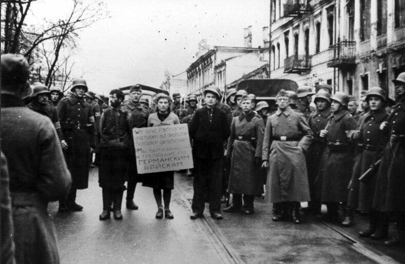 """Masha Bruskina, une infirmière faisant partie de la résistance soviétique, est conduite dans les rues de Minsk, en Biélorussie, avant sa pendaison, le 26 octobre 1941. Elle doit porter une pancarte avec l'inscription """"Nous sommes les partisans qui tirons sur les soldats allemands""""."""