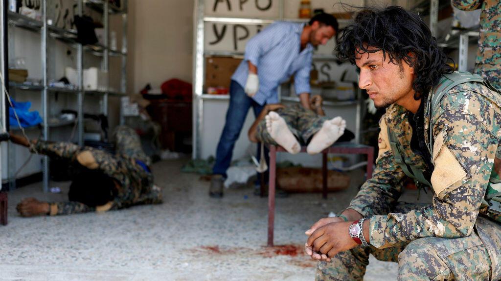 En plena guerra, un fotógrafo graba el momento en que un combatiente de las fuerzas democráticas sirias se sienta a esperar mientras médicos atienden a sus camaradas heridos por francotiradores del Estado Islámico.