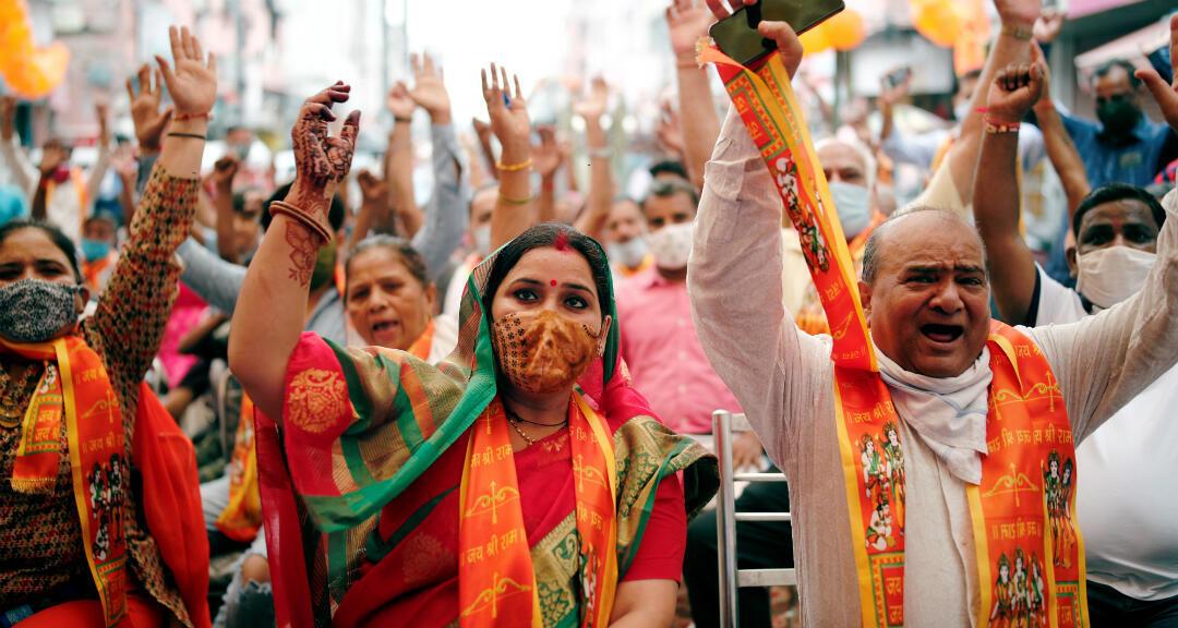Ciudadanos cantan consignas durante una proyección en vivo de la ceremonia de colocación de piedras en el lugar donde se construirá el nuevo templo al dios Ram. Nueva Delhi, India, el 5 de agosto de 2020.