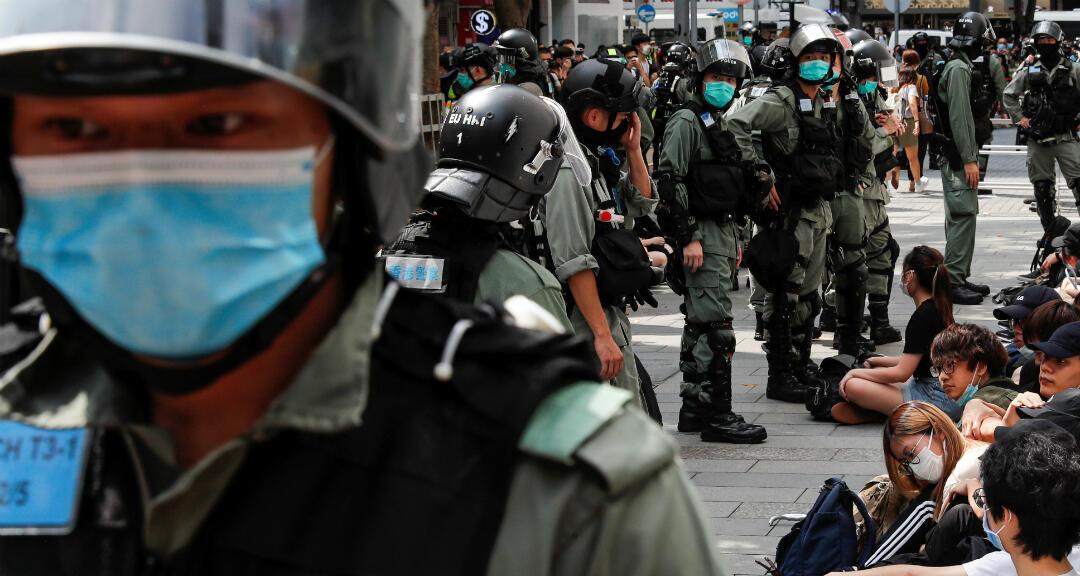 Un grupo de manifestantes el 27 de mayo de 2020 en Hong Kong tras haber sido detenidos en una redada policial durante una protesta mientras se debate en el Parlamento la aprobación de una ley que busca penalizar las burlas al himno nacional chino.