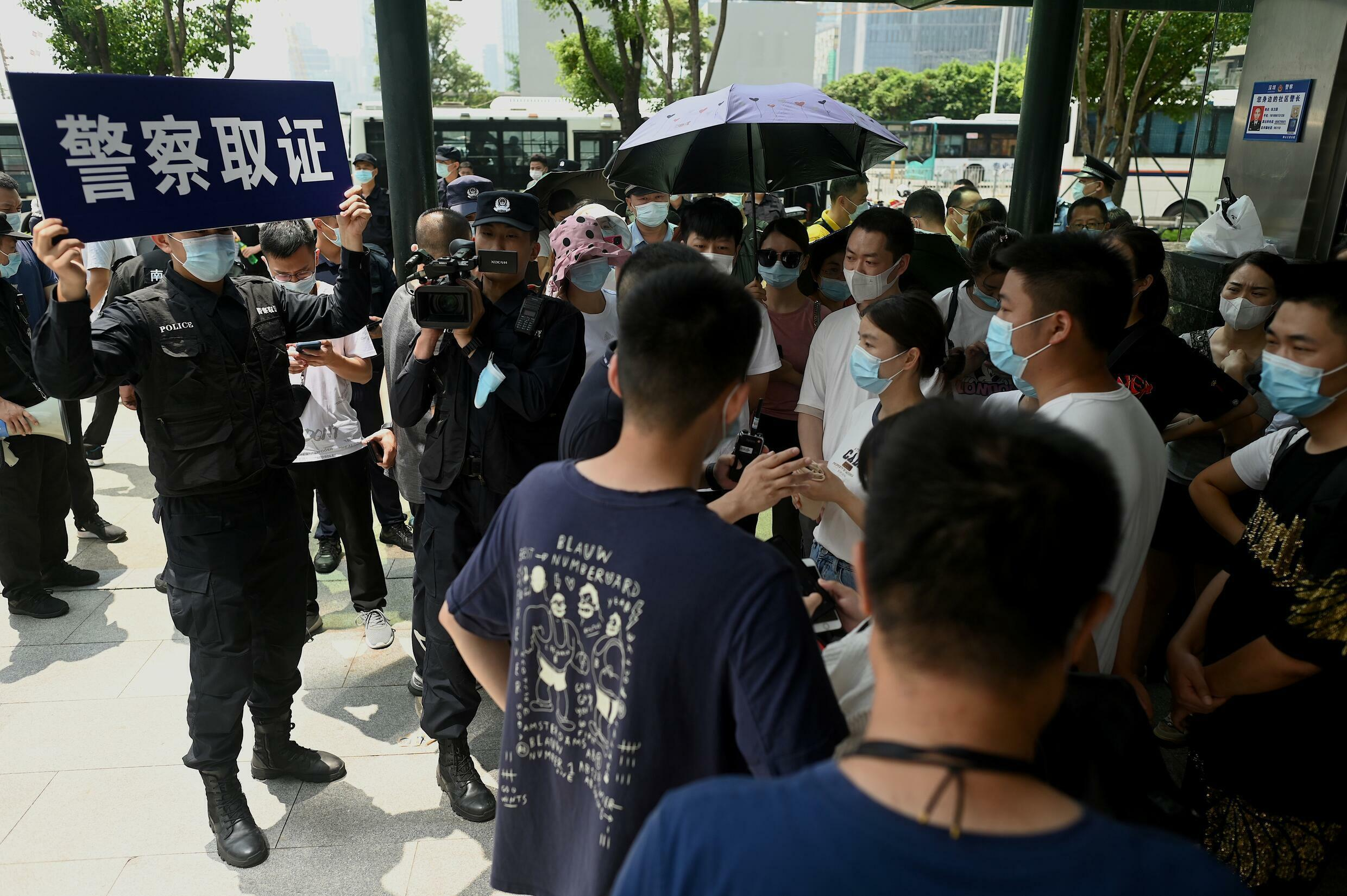 Police officers frame protesters gathered outside Evergrande headquarters in Shenzhen on September 16, 2021