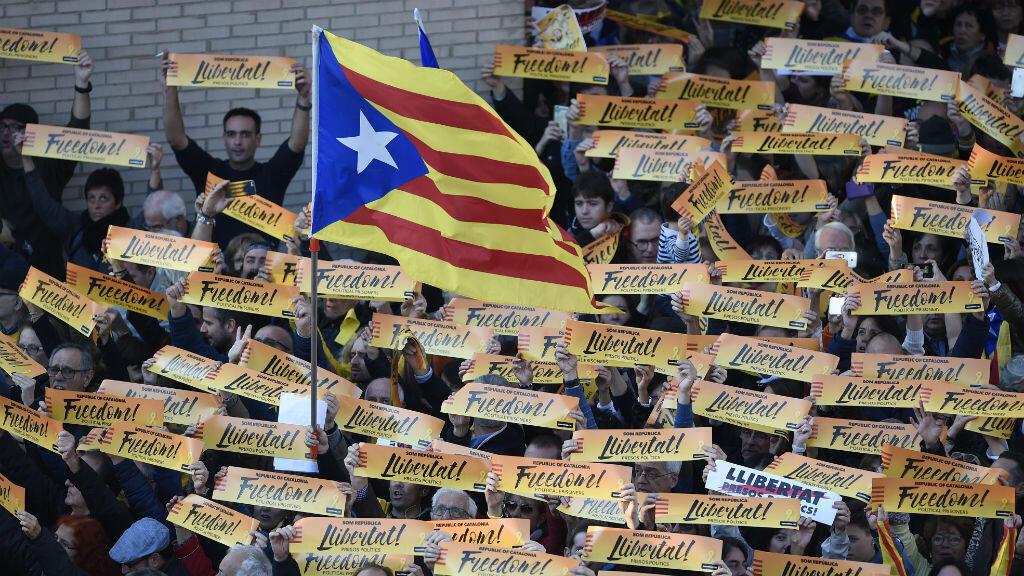 """Un hombre sostiene una bandera catalana a favor de la independencia, mientras que otros ciudadanos levantan carteles de """"libertad"""" durante una manifestación en Barcelona el 11 de noviembre  pidiendo la liberación de los líderes separatistas encarcelados."""