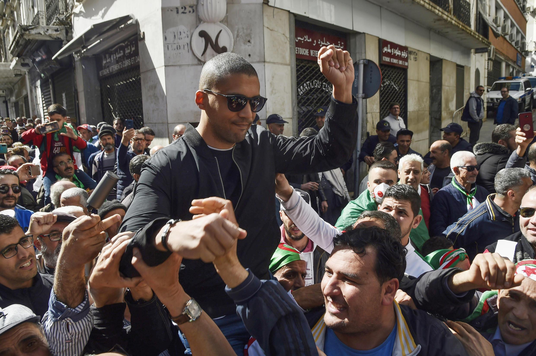 Photo d'archives du journaliste algérien Khaled Drareni, aujourd'hui emprisonné, porté par des manifestants après avoir été brièvement détenu par les forces de sécurité à Alger, le 6 mars 2020