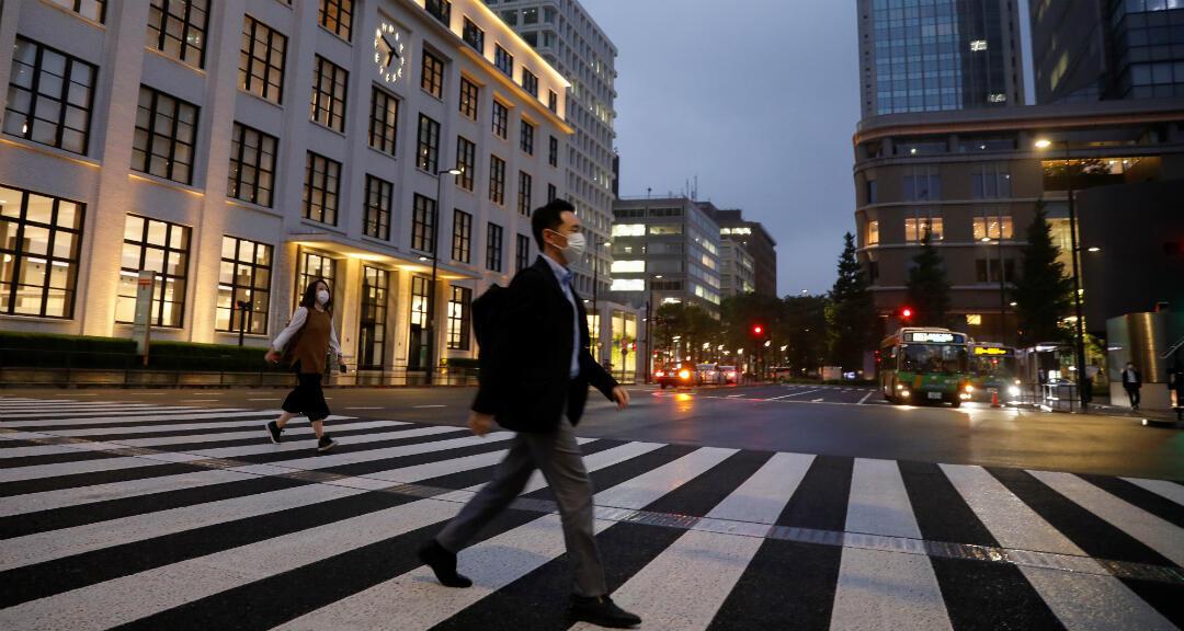 Un peatón con una mascarilla cruza una calle, en medio del brote de coronavirus en el distrito financiero de Tokio, Japón, el 21 de mayo de 2020.