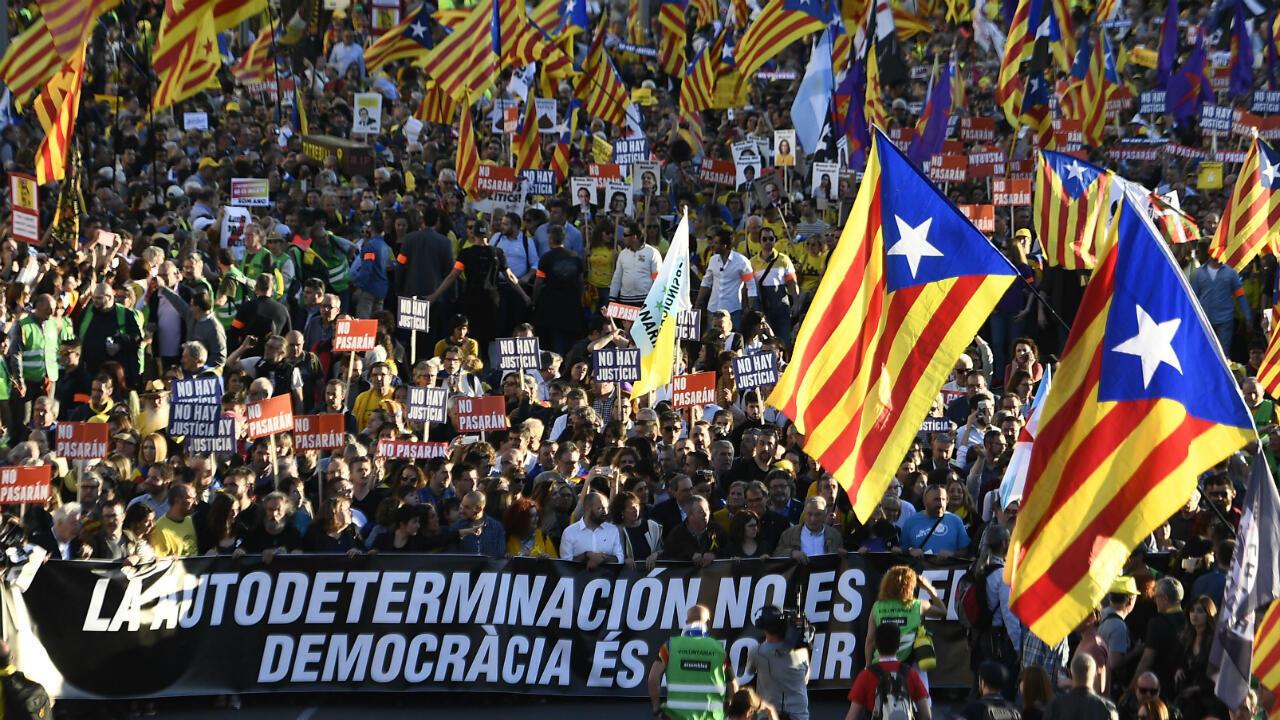 """Manifestantes ondean banderas a favor de la independencia de Cataluña y una pancarta con el mensaje """"La autodeterminación no es un crimen, la democracia es una decisión"""", como protesta contra el juicio a los líderes separatistas catalanes. Madrid, España, el 16 de marzo"""