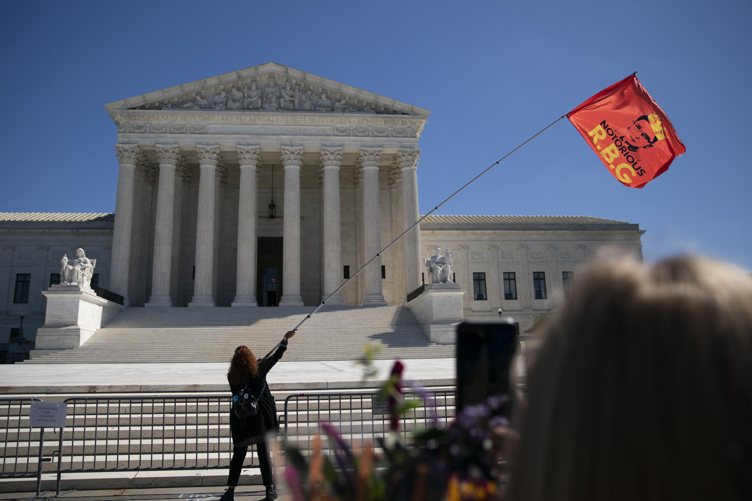 A woman waves an 'RBG' flag outside the US Supreme Court at a makeshift memorial for late Supreme Court Justice Ruth Bader Ginsburg on Sept. 21, 2020.