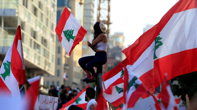 Una manifestante sostiene la bandera nacional durante una protesta contra el Gobierno en Beirut, Líbano, el 20 de octubre de 2019. REUTERS /