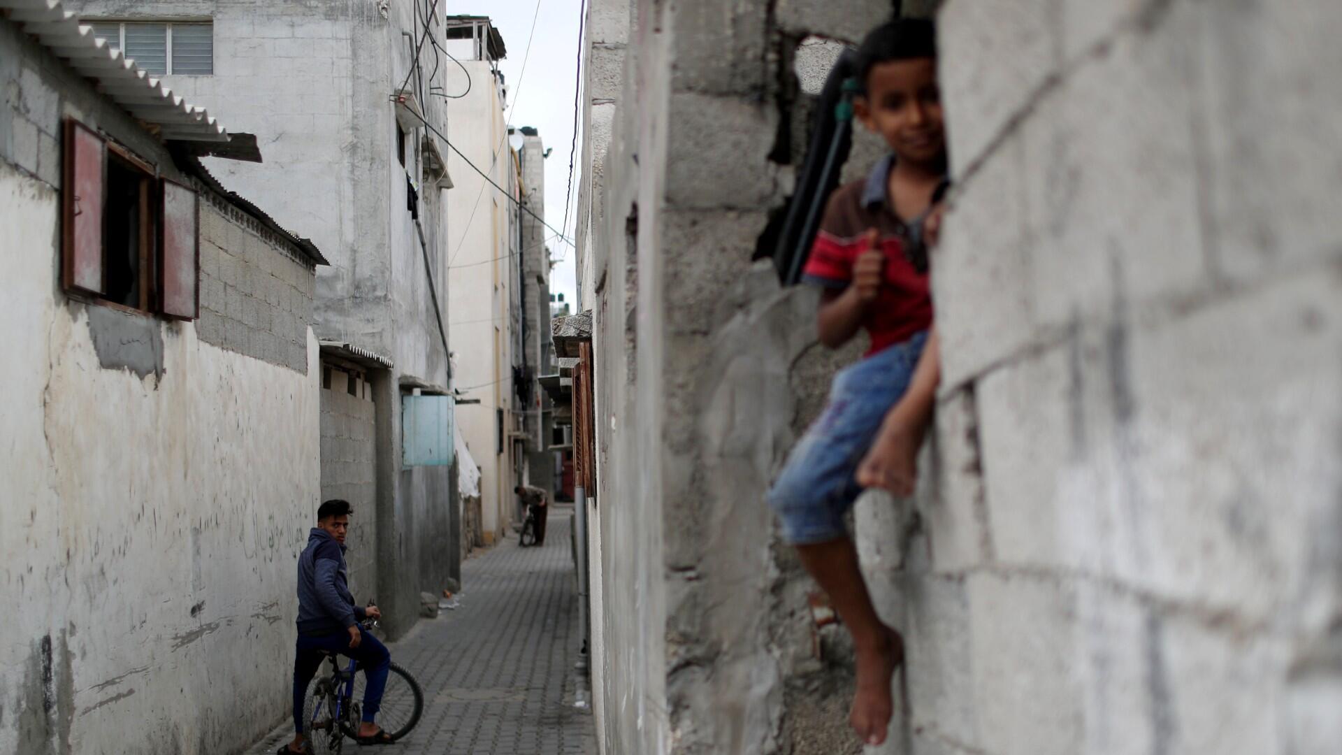 Jóvenes palestinos en bicicleta observan a un niño sentado en una pared en el campo de refugiados de Jabalia, una de las áreas más densamente pobladas del mundo, en medio de las preocupaciones sobre la propagación de la enfermedad por coronavirus (COVID-19), en el norte de la Franja de Gaza 5 de mayo de 2020.