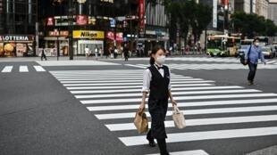 Una mujer con mascarilla cruza un paso de peatones en Tokio el 20 de julio de 2020
