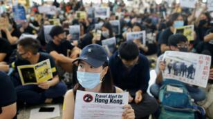 Les manifestants brandissent des pancartes face aux voyageurs, arrivant à l'aéroport international de Hong Kong, le 9 août 2019.