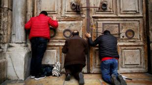 Los fieles se arrodillan y oran frente a las puertas cerradas de la Iglesia del Santo Sepulcro en la Ciudad Vieja de Jerusalén, el 25 de febrero de 2018.