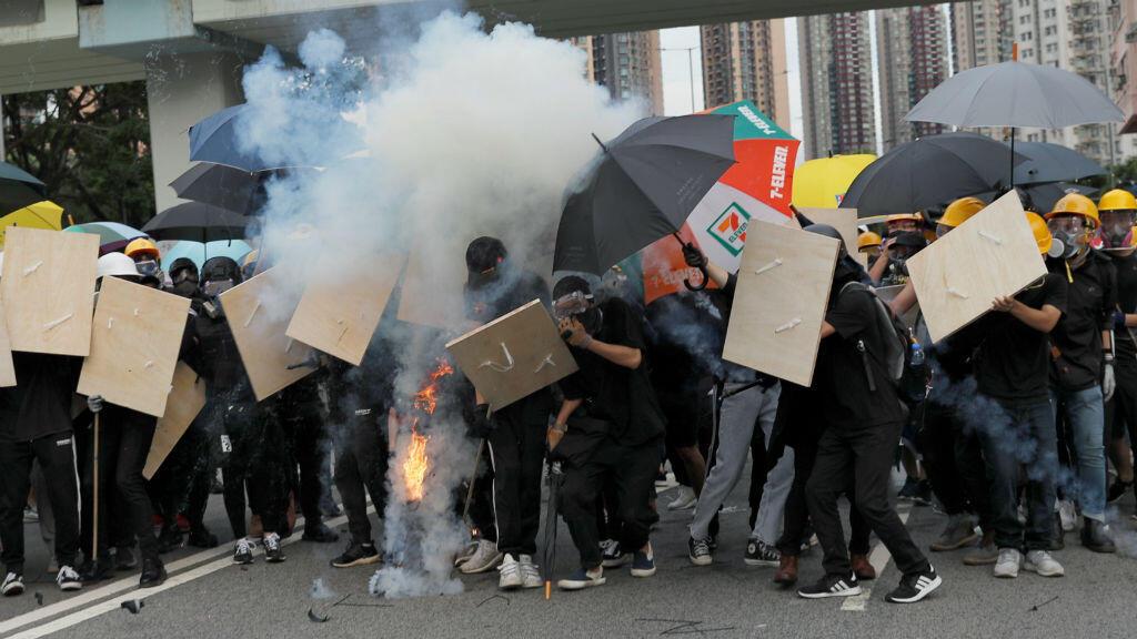 Manifestantes reaccionan cuando la policía antidisturbios dispara gases lacrimógenos durante una protesta en Hong Kong el 27 de julio de 2019.