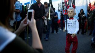 Un estudiante toma una foto de un títere que representa al presidente de Argentina, Mauricio Macri, durante una protesta que exige mejores salarios para los maestros y más presupuesto para las universidades, en Buenos Aires, el 16 de mayo de 2019.