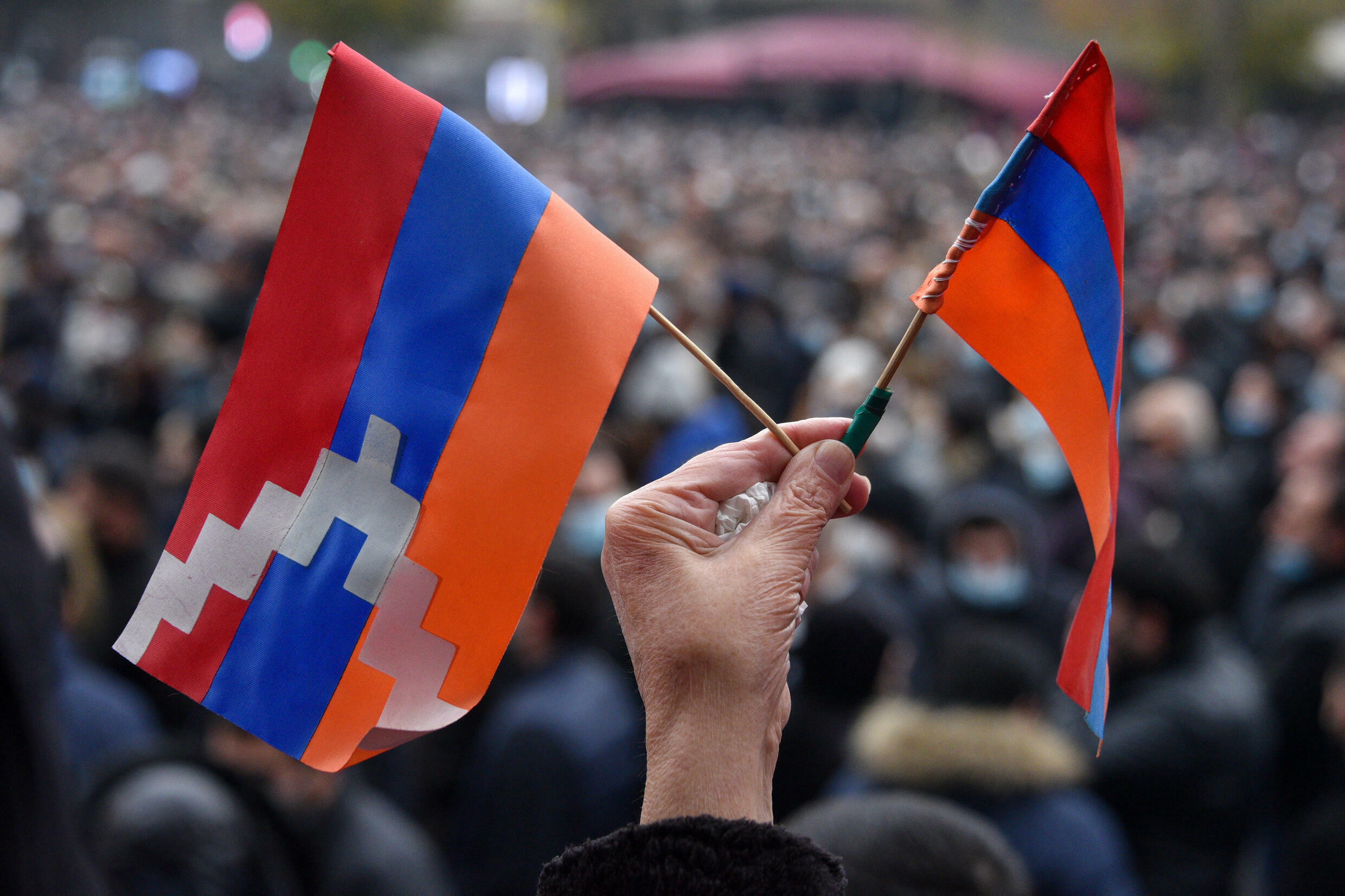 A woman holds a flag (L) of the breakaway Nagorno-Karabakh region and an Armenian flag (R) during a rally against a controversial peace agreement with Azerbaijan in Yerevan on December 5, 2020