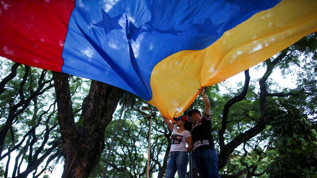 Manifestantes agitan un bandera de Venezuela fuera del Palacio San Martín antes de una conferencia de prensa del líder de la oposición, Juan Guaido, en Buenos Aires, Argentina, el 1 de marzo de 2019.