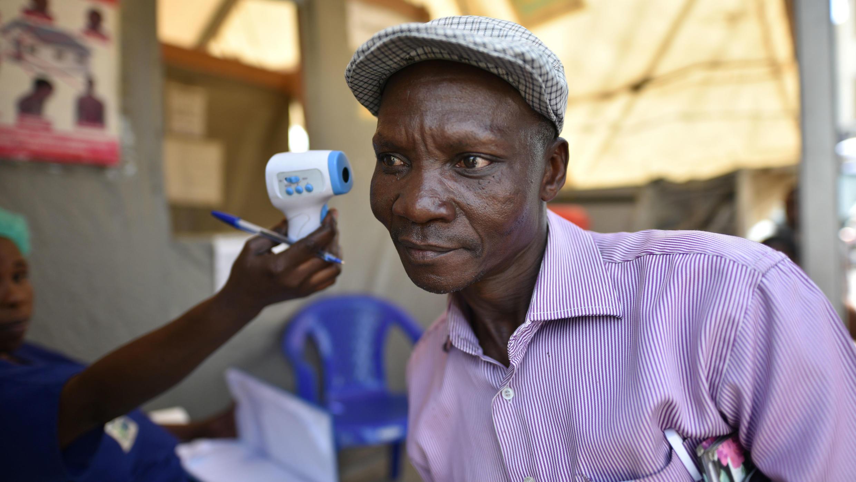 Un trabajador de salud verifica la temperatura de un hombre como parte de la evaluación del ébola al ingresar al Hospital General de Goma, República Democrática del Congo, 15 de julio de 2019.