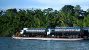 """Un barco transporta camiones de petróleo por el río Napo, en Tiputini, Ecuador. Porta la advertencia de """"peligro"""". 10/20/2017"""