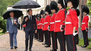 French President Emmanuel Macron and UK's Prince Charles inspect a guard of honour at Clarence House, London on June 18, 2020.