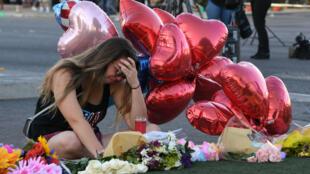 Une femme en pleurs, mardi 3 octobre 2017, devant un mémorial improvisé sur le strip de Las Vegas.